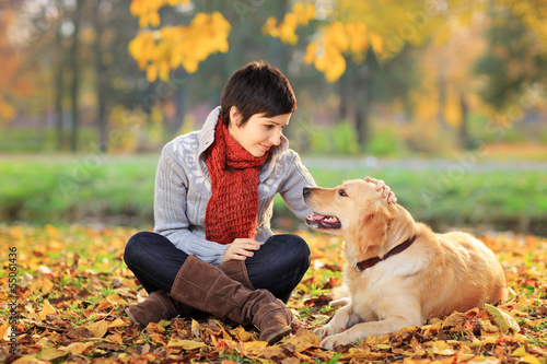 Young woman in a park stroking her dog