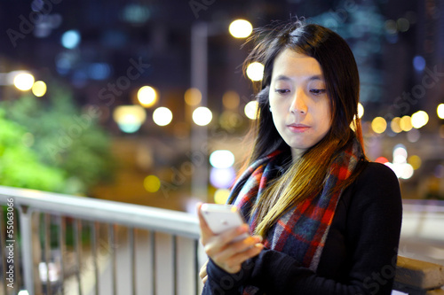Asian woman using mobile at night