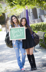 Mixed Race Female Students Holding Back To School Chalkboard