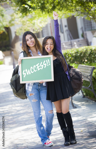 Female Students Holding Chalkboard With Success Written on it.