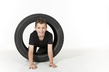 Young boy is climbing through a tire