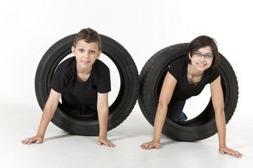 A boy and a girl are climbing through tires