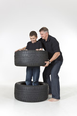 Father and son are playing with tires