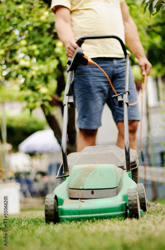 Man moves with lawnmower & mows green grass
