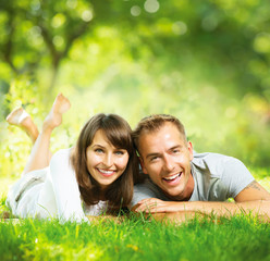 Happy Smiling Couple Together Relaxing on Green Grass Outdoor
