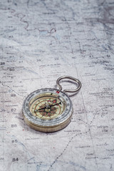Old compass on a cartographic map of mountains