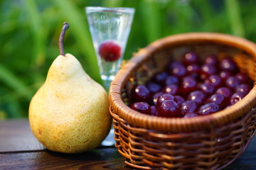Pear and wicker basket with cherries