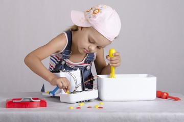Девочка ремонтирует игрушечную мелкую бытовую технику
