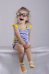Two-year-old girl in funny glasses sits and laughs cheerfully