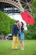 Couple with red umbrella under the Eiffel tower