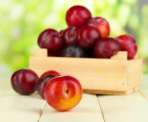 Ripe plums in wooden box on wooden table on natural background