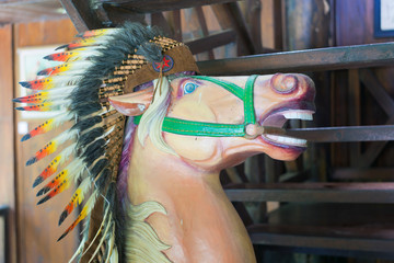 Head of horse statue with an Indian headdress of feathers