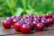 Wet cherry on a wooden plank on a green blurred background