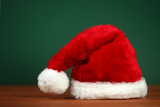 Red Santa Hat With Copy Space on Green and Wood Background