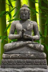 Grey Buddah with bamboo bachground