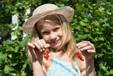 Handsome little girl with bunch of red currants