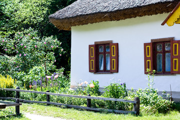 An old Ukrainian rural hut and flowerbed