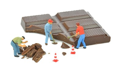 Miniature workmen breaking a bar of chocolate with hammers