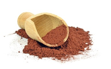 A wooden scoop with cocoa powder on a white background