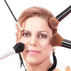 Pretty mid adult woman with makeup brushes