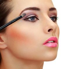 Eyes makeup. Brush applying eye shadows on beauty woman face. Cl