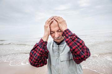 Elderly man suffering from a headache on sea background