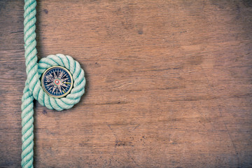 Compass and rope on wooden texture background