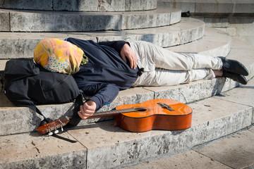 suonatore ambulante che dorme sdraiato su scalinata