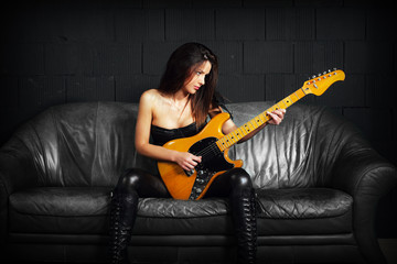 Female guitarist sitting on a leather couch