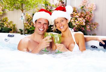 Happy Christmas santa couple in jacuzzi.