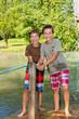 Zwei glückliche Freunde überqueren einen Bach mit dem Floß