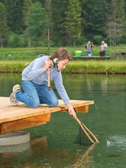 Junge angelt - keschert Forelle am Fischteich