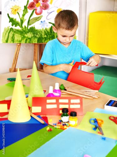 Boy cut paper in preschool.