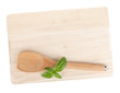 Cooking utensil and basil leaves over cutting board