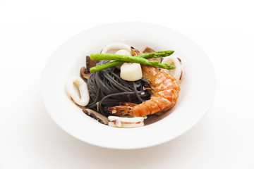 Black spaghetti with seafood on white background (squid ink past