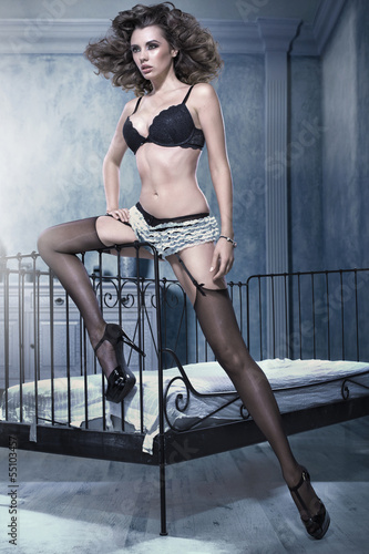 Sexy brunette woman leaning on bed frame