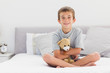 Smiling little boy sitting on bed holding his teddy bear