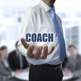 Smart businessman holding the word coach