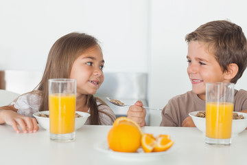 Siblings looking at each other during breakfast