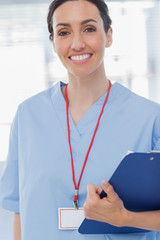 Smiling nurse holding files and looking at camera