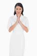 Elegant dark haired model with white dress joining hands