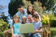 Smiling multi generation family with a laptop sitting in park