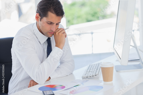 Concentrated businessman analyzing graphs