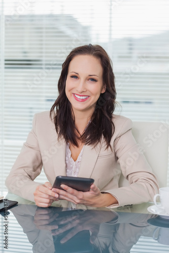 Smiling businesswoman working on her tablet pc