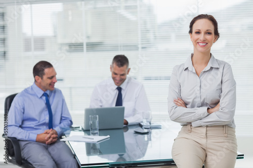 Happy businesswoman posing leaning against the desk