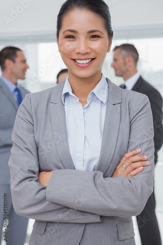 Businesswoman posing while colleagues talking together
