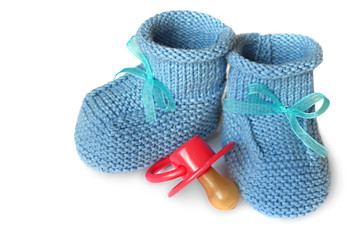 pair of blue knit children's bootees and baby's dummy