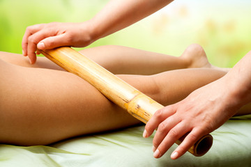 Hands massaging female legs with bamboo.