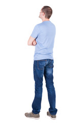 Back view of young man in t-shirt and jeans  looking.
