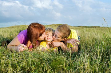 Parents kissing their daughter lying on a green meadow